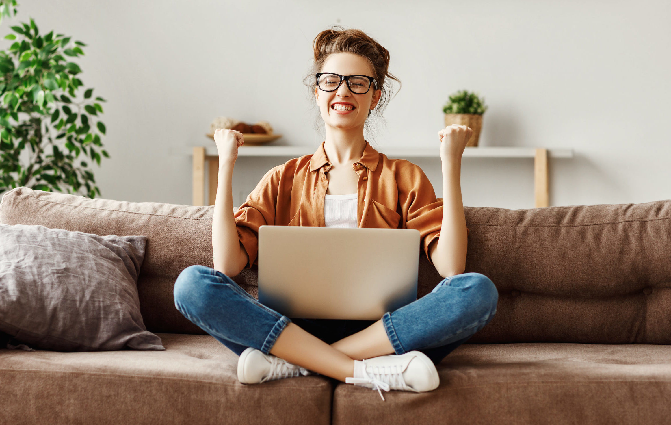 Delighted young woman celebrating victory in online lottery