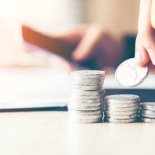 Businessman hand putting stack of coin money cover growing plant for the investment financial report.  Investment concept..